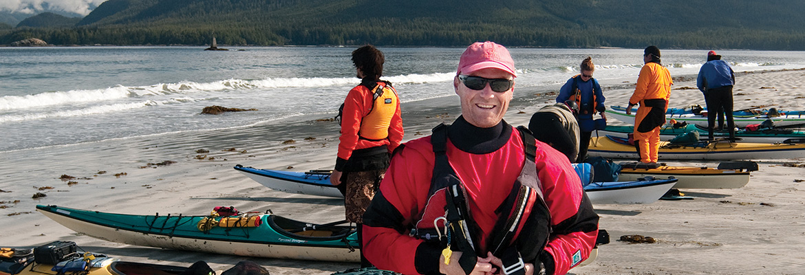 NIC instructor on beach with kayaks