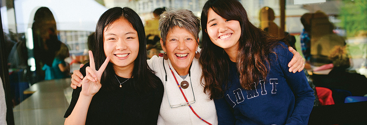 Two international students stand with their homestay host