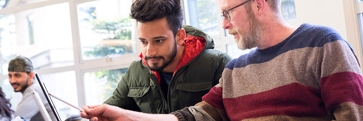 NIC instructor Ben Hecht provides free, drop-in writing support to student Jagmeet Singh in NIC's Library and Learning Commons