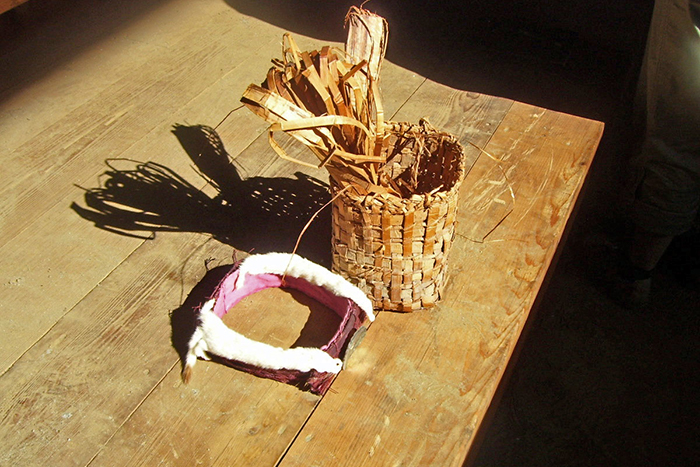 Woven cedar basket and indigenous head dress sitting on table.