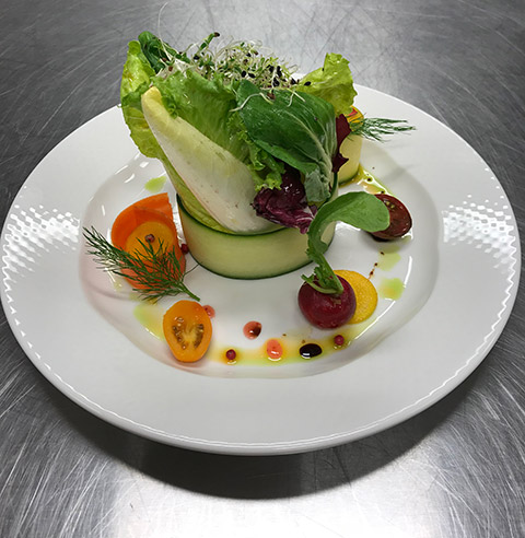Salad plate with variety of lettuces, cherry tomatoes and cucumber slices